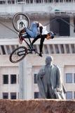 Il ciclista in mountain-bike fa un'acrobazia davanti al monumento di Lenin Immagini Stock