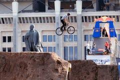 Il ciclista in mountain-bike fa un'acrobazia davanti al monumento di Lenin Fotografia Stock