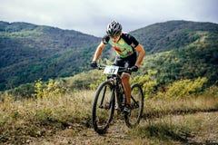 Il ciclista in mountain-bike maschio dell'atleta guida la traccia di montagna Immagini Stock