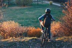 Il ciclista in mountain-bike sta sull'orlo di una collina al tramonto prima dello sbarazzato di immagini stock libere da diritti