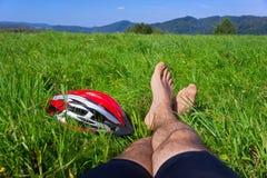 Il ciclista si rilassa su erba in montagne Fotografie Stock