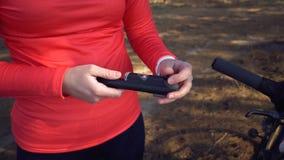 Il ciclista turistico del giovane atleta caucasico della donna utilizza gli attrezzi per bricolage, una pompa di bicicletta per g immagini stock