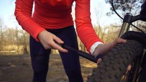 Il ciclista turistico del giovane atleta caucasico della donna utilizza gli attrezzi per bricolage, una pompa di bicicletta per g immagine stock
