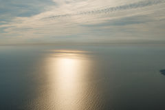 Il cielo blu con le nuvole e l'aeroplano trascina sopra il Mar Nero Il treno di Sun sulla superficie del mare e su una barca con  Immagine Stock Libera da Diritti