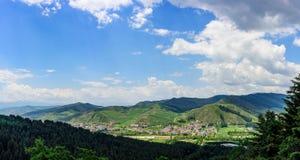 Il cielo blu, le nuvole bianche, le montagne verdi e l'erba suonano intorno al bello villaggio Fotografia Stock Libera da Diritti