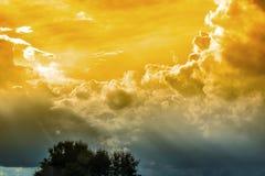 Il cielo con il sole splende attraverso i precedenti delle nuvole di pioggia Immagini Stock