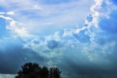 Il cielo con il sole splende attraverso le nuvole di sera Immagini Stock