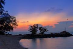Il cielo crepuscolare arancio alla spiaggia con due alberi sul cente Fotografia Stock