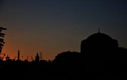 Il cielo drammatico di sera in Oriente, moschee ed antenne Immagini Stock