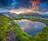 Il cielo drammatico ha riflesso in piccolo lago in alpi svizzere Fotografia Stock