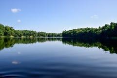 Il cielo e gli alberi dell'estate hanno riflesso in acqua del lago immagini stock libere da diritti