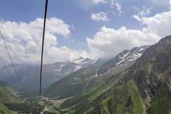 Il cielo nel verde delle nuvole e la neve sulle montagne e sull'ascensore cablano, regione del nord di Caucaso Elbrus Fotografie Stock Libere da Diritti