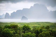 Il cielo nuvoloso e la nebbia coprono l'isola vicino alla spiaggia Fotografia Stock