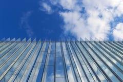 Il cielo nuvoloso ha riflesso nella parete di vetro di una costruzione moderna Immagine Stock