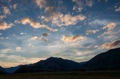 Il cielo si appanna le montagne del tramonto Immagine Stock