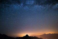 Il cielo stellato meraviglioso su tempo di Natale e sulla gamma di alta montagna maestosa delle alpi italiane, con i villaggi d'a Immagini Stock Libere da Diritti