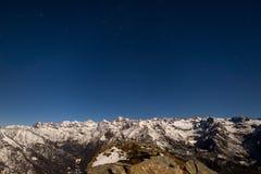 Il cielo stellato sopra le alpi nell'inverno nell'ambito di luce della luna Fotografia Stock