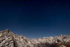 Il cielo stellato sopra le alpi nell'inverno nell'ambito di luce della luna Fotografie Stock Libere da Diritti