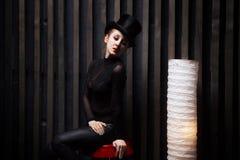 Il cilindro d'uso della donna si siede sulla sedia in una stanza scura Fotografia Stock Libera da Diritti