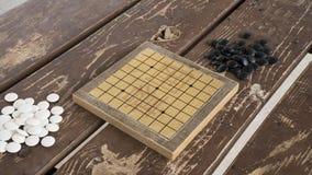 Il cinese gioco da tavolo di Weiqi o va Pietre in bianco e nero e piccolo bordo fatto a mano Fotografia Stock Libera da Diritti