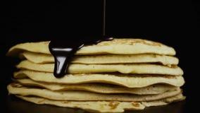 Il cioccolato è versato su un pancake contro un fondo nero Movimento lento video d archivio