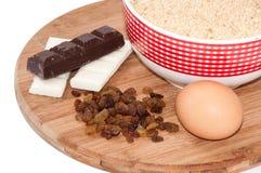 Il cioccolato bianco e nero, l'uva passa, l'uovo ed il biscotto a terra agglutinano Immagine Stock