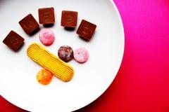 Il cioccolato e le lecca-lecca sono su un piatto bianco fotografia stock libera da diritti
