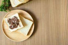 Il cioccolato si è sparso sulla fetta di pane sul piatto di legno Immagine Stock