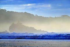 Il ciottolo e la spiaggia sabbiosa durante l'alba, con le onde blu scuro e le nuvole arancio, Se di penombra di mattina della cos immagine stock