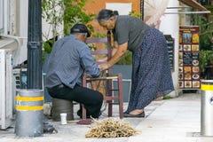 IL CIPRO, NICOSIA - 10 GIUGNO 2019: Coppie greche anziane degli artigiani che fanno le sedie di vimini su una via della città Fam fotografia stock libera da diritti