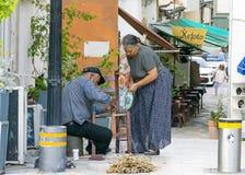 IL CIPRO, NICOSIA - 10 GIUGNO 2019: Coppie greche anziane degli artigiani che fanno le sedie di vimini su una via della città r fotografie stock