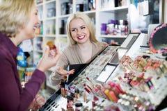 Il cliente affascinante positivo della donna sceglie i cosmetici Immagini Stock Libere da Diritti