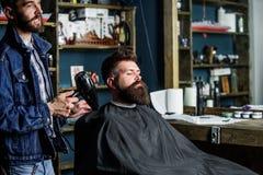 Il cliente barbuto dei pantaloni a vita bassa ha ottenuto l'acconciatura Il barbiere con hairdryer scarica i capelli da capo Conc immagini stock