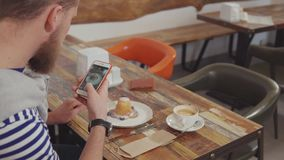 Il cliente della caffetteria sta fotografando il dessert delizioso sulla tavola archivi video
