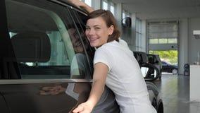 Il cliente della ragazza gode dell'acquisto, il compratore felice del ritratto, il concessionario auto, la nuova automobile di ac stock footage