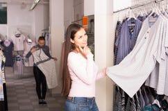 Il cliente femminile che seleziona il sonno copre del departme della biancheria intima Fotografie Stock
