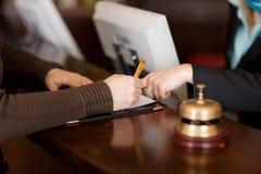 Il cliente femminile d'assistenza del receptionist nel riempire forma Immagini Stock Libere da Diritti