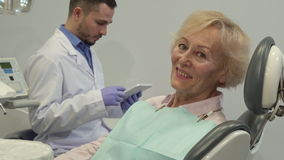 Il cliente femminile mostra il suo pollice su sulla sedia dentaria stock footage