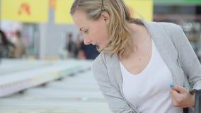 Il cliente femminile sceglie i prodotti semilavorati che sono immagazzinati nel frigorifero stock footage