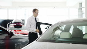 Il cliente femminile viene all'automobile, il consulente in materia del venditore dice circa l'automobile stock footage