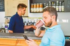 Il cliente ha ottenuto la sua bevanda Abbia sorsata di energia Il cliente dell'uomo con la barba gode del caffè in tazza di carta fotografia stock libera da diritti