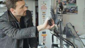 Il cliente ispeziona il motociclo nel negozio video d archivio