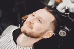 Il cliente maschio lava il suoi negozio di barbiere dei capelli e sorrisi, la designazione alla moda fotografia stock libera da diritti