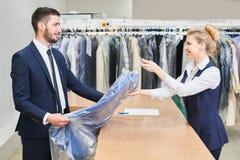Il cliente maschio prende ad un lavoratore della lavanderia della donna i vestiti puliti Fotografia Stock