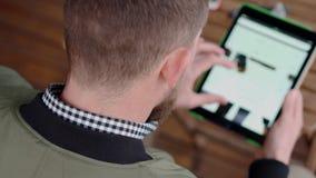Il cliente maschio sta scegliendo le scarpe in deposito online, passante in rassegna il sito internet stock footage
