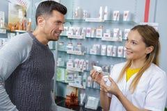 Il cliente maschio vuole comprare la crema dal farmacista professionista fotografia stock libera da diritti