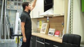 Il cliente nel negozio di mobili ottiene interessato in cucina Lui che apre le porte archivi video