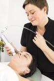 Il cliente ottiene i trattamenti del fronte alla clinica di bellezza Fotografia Stock