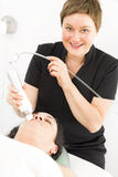 Il cliente ottiene i trattamenti del fronte dal terapista sorridente Immagini Stock Libere da Diritti