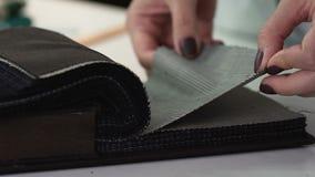 Il cliente passa la scelta del tessuto per le coperture nel negozio, tessuto della mobilia del vestito stock footage